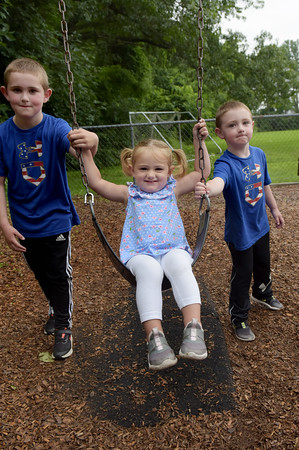 TIM JEAN/Staff photo<br /> <br /> Cameron Quinlan, 6, left, and his brother Calvin, 4, push their sister Caroline, 2, on the swings in the Penguin Park Playground in Andover, after the heavy rains stopped on Tuesday afternoon.     7/13/21