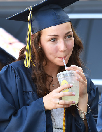 CARL RUSSO/staff photo Andover graduate Sarah Kelly stays cool with a cup of ice cold lemonaide. Crack'd Kitchen & Coffee gourmet eatery in Andover provided  hundreds of lemonade drinks for the graduates and staff before the ceremony.  Andover High School held its 161Commencement Monday afternoon.  6/7/2021