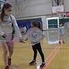 TIM JEAN/Staff photo<br /> <br /> Student instructor Adelaide Weeden, left, shows Nora Kline how to swing the racket properly during the Pee Wee Tennis class. Children learned basic fundamentals during the Andover Recreation learn to play tennis program at South School.  3/15/21