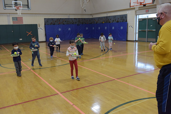 TIM JEAN/Staff photo<br /> <br /> Children ages 4-6 in the Pee Wee Tennis class walk towards instructor Mike Fay as they learn basic fundamentals during the Andover Recreation learn to play tennis program at South School.  3/15/21