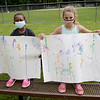 TIM JEAN/Staff photo<br /> <br /> Noelle Wright, left, and Annabelle Palmer, both 8, show off their finish spray paint artwork made in the morning during a summer camp program run by Andover Recreation Department held at Recreation Park.    8/26/20