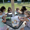 TIM JEAN/Staff photo<br /> <br /> Crafters sit under an umbrella from left to right, Aubrey Mohamed, 6, Shannon Larney, 19, camp councilor, Mariella Berger, 7, Penny Kaminsky, 6, Songy Choi, 17, camp councilor, and Genevieve Berger, 7, during a summer camp program run by Andover Recreation Department held at Recreation Park.    8/26/20