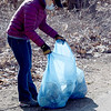 TIM JEAN/Staff photo<br /> Rachael Pick, of Salem, NH., places a trash bag full of debris along the paved edge during the Derry Rail Trail Alliance annual spring cleanup. Derry DPW later picked up all the trash bags along the trail. About twenty volunteers split into three groups and picked up debris along the trail starting in downtown Derry, NH., towards the Londonderry and Windham trail sections.   4/3/21