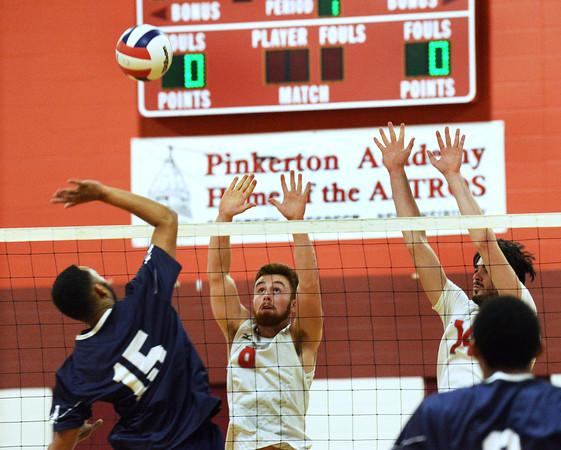 CARL RUSSO/Staff photo. Pinkerton's captain, Brian Castle, left and Matt Fabrizio keep their eyes on the ball as Lawrence's Andre Wilson hits it over the net. Lawrence high defeated Pinkerton Academy in boys volleyball action Saturday afternoon. 4/28/20188