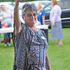 TIM JEAN/Staff photo<br /> <br /> Marjorie Palmer raisers her hand to make a bid and win the $1000 valued Texas BBQ dinner catered by Gabi's Smokeshack during the Community Caregivers of Greater Derry 30th anniversary barbecue at the Mack's Apples U-Pick station 2.    8/4/18