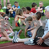 CARL RUSSO/staff photo. DERRY NEWS: Bob Mullen, a member of the Greater Derry Track Club leads the seven and eight year old runners in a stretching routine before running. Greater Derry Track Club hosted their 43rd. annual youth Fun Runs at Londonderry high last Monday. 7/02/2018