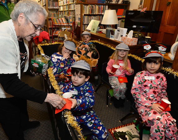 CARL RUSSO/Staff photo. Taylor Library assistant director, Fran Mears offers a Christmas cookie to David DiRico, 4 and other passengers of the Polar Express. This is Mears last ride on the Polar Express. She is retiring after 20 years at the library. Taylor Library in East Derry hosted its annual Polar Express story time Thursday night. 12/12/2019