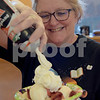 TIM JEAN/Staff photo<br /> <br /> Nancy Vigezzi, Assistant Director at the Nesmith Library, adds whipped cream to a strawberry shortcake during the 36th Annual Strawberry Festival, and Windham's Nutfield 300th celebration.      6/1/19