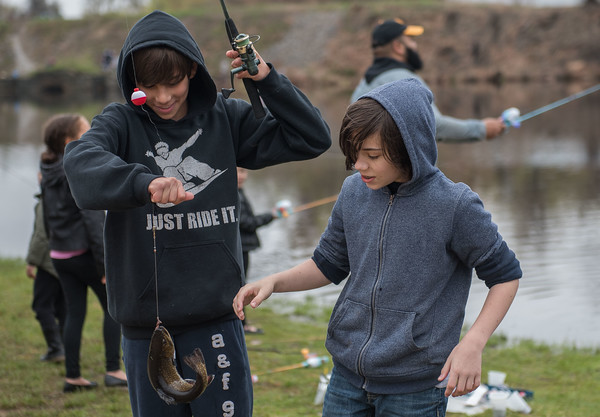 AMANDA SABGA/Staff photo<br /> <br /> Anthony Dube and PJ Shattuck, both 12 of Derry look at a fish caught during the Annual Fishing Derby at Hood Park during the Downtown Derby Day event in Derry, NH.<br /> <br /> 5/4/19