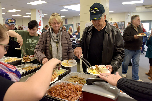 TIM JEAN/Staff photo <br /> <br /> US Navy veteran Paul Fortin, right, and his wife Marilyn, of Derry, fill up a plate in the buffet style breakfast during a Veterans Breakfast at Londonderry High School.    11/9/19