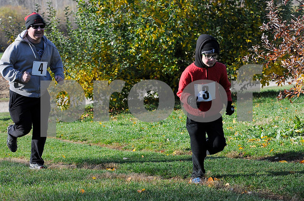 TIM JEAN/Staff photo<br /> <br /> Randy Williams, left, of Londonderry, run with his son Theo, 9, as they make their way through the apple orchard during North Londonderry School first annual Fall Fun Run held at Mack's Apples. 11/2/19