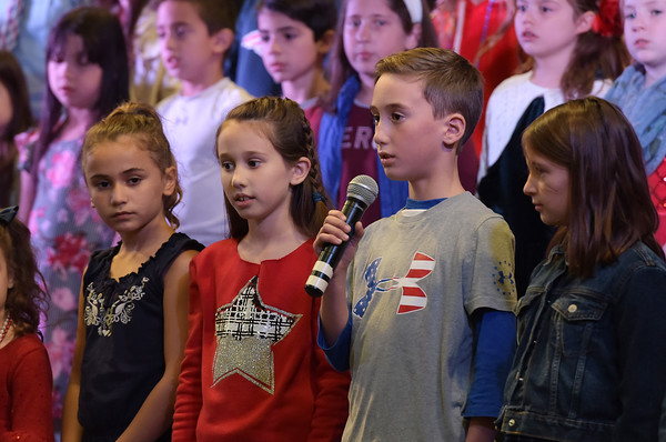 TIM JEAN/Staff photo <br /> <br /> Third-grader Ben Hazel, with mic, speaks his part of a Veterans Day Poem on stage during the annual Veterans Day assembly at Golden Brook Elementary School in Windham.     11/8/19