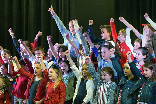 TIM JEAN/Staff photo <br /> <br /> Third-grader raise their arms as they sing God Bless America on stage during the annual Veterans Day assembly at Golden Brook Elementary School in Windham.     11/8/19