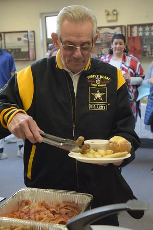 TIM JEAN/Staff photo <br /> <br /> Wayne Tumber, an Army Purple Heart Vietnam Veteran, of Londonderry, fills his plate during a Veterans Breakfast at Londonderry High School.    11/9/19