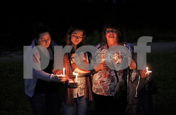 MIKE SPRINGER/Staff photo<br /> Shannon Vallante, second from left, of Derry holds a photograph of herself with her husband, Joseph Aaron Vallante, who died by suicide on Nov. 28, 2018, as she stands beside her sister, Paige Gifford, left, and her mother, Lori Gifford, and her brother, Joseph Gifford, 9, during a suicide and addiction awareness vigil Thursday evening at MacGregor Park in Derry.<br /> 8/29/2019