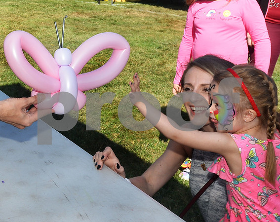 CARL RUSSO/Staff photo. Sarah Pottle of Derry and her daughter Teigan, 3, reach for the butterfly balloon made for her by party professional, Joe Tombarello of Silly Solutions.   <br /> <br /> The 30th annual Derryfest was held Saturday in MacGregor Park. The park was full of booths, entertainment on stage, businesses under tents etc. The  300th anniversary of Nutfield  time capsule and its contents was on display at the Derry Heritage Commission booth.  9/21/2019