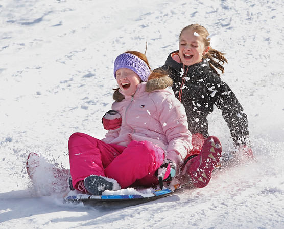 MIKE SPRINGER/Staff photo<br /> Jillian Whitney, left, of Atkinson and her friend Miranda Solt of Salem, both 10, have fun sledding down the hill Sunday during the 21st annual Frost Festival at Alexander-Carr Park in Derry.<br /> 2/16/2020