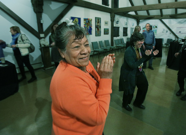"MIKE SPRINGER/Staff photo<br /> Carmen Ayala, an immigrant from Peru now living in Manchester, claps to the music during the opening reception last Thursday for ""Our Neighbors, Ourselves,"" an art exhibit on the theme of immigration hosted by St. Peter's Episcopal Church in Londonderry. In the background is Cecelia Fernandez-Hall of Windham.<br /> 1/21/2020"