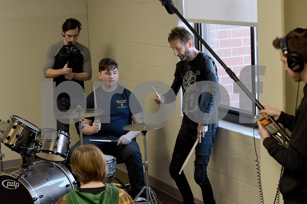 """TIM JEAN/Staff photo <br /> <br /> Godsmack drummer Shannon Larkin, right, works with  Hood Middle School student Rui Hernandez, seated as students learn part of a song before filming a video for  """"Unforgettable.""""      2/14/20"""