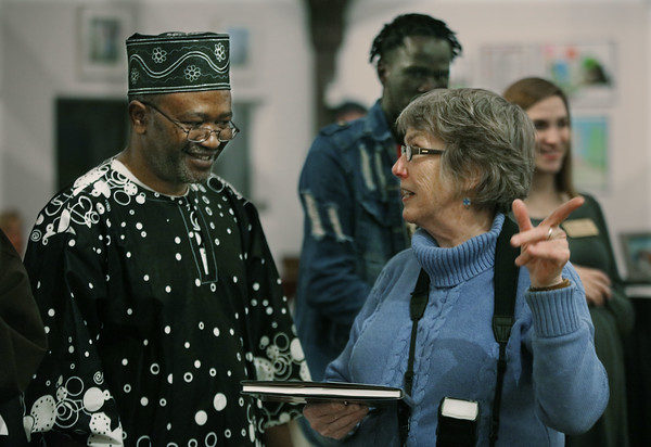 """MIKE SPRINGER/Staff photo<br /> Exhibiting artists Segun Olorunfemi of Manchester and Becky Field of Concord visit during the opening reception last Thursday for """"Our Neighbors, Ourselves,"""" an art exhibit on the theme of immigration hosted by St. Peter's Episcopal Church in Londonderry. Olorunfemi, an immigrant from Nigeria, is a painter; Field, a photographer, has published a book on immigrants.<br /> 1/21/2020"""