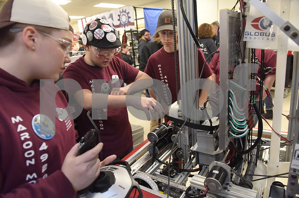 TIM JEAN/Staff photo <br /> <br /> Whittier Tech's Grace Portal, 14, left, James Gorman, 15, and Caleb Cook, 17, test out a solution on the schools team robot in the pit area during the FIRST Robotics New England Granite State District event held at Salem High School.   2/29/20