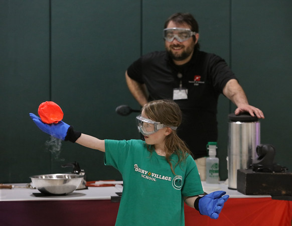 MIKE SPRINGER/Staff photo<br /> Second-grader Sophia McClory holds a balloon after it was super-cooled by liquid nitrogen during a presentation Tuesday at Derry Village Elementary School on the states of matter by Jonah Sidman, background, of the Museum of Science.<br /> 2/18/2020