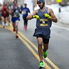 CARL RUSSO/staff photo. Warren Bartlett, 22 of Loudon N.H. checks his time as he approaches the finish line to capture first place with a time of 4:04.9. Bartlett, who has participated eight years in a row, ran his first race as a junior high student.<br /> <br /> The 21st. Annual New Year's Day Millennium Mile road race was held on New Year's Day at Londonderry high. Just over 1400 runners of all ages consisting of serious runners to family fun runners participated. 1/1/2020.