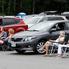 TIM JEAN/Staff photo<br /> <br /> People sit in chairs near the vehicles as members of Pinkerton Players perform on stage during a drive-in performance of the show Children of Eden. The show was held outside at the Tupelo Music Hall because of the coronavirus.    7/22/20