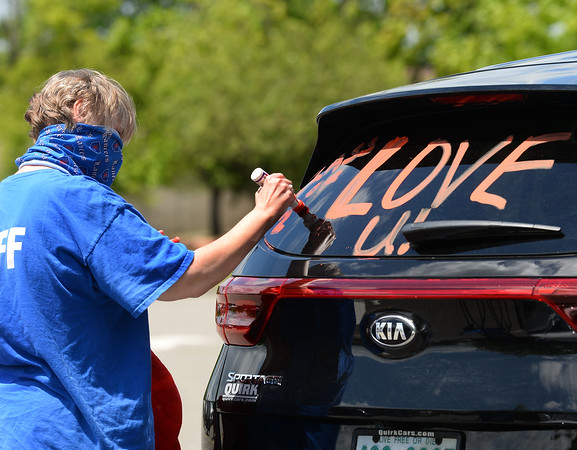 CARL RUSSO/staff photo. Joanne Blake, a Londonderry high school math teacher for over 30 years, decorates her car as she gets ready to salute the seniors. <br /> <br /> Londonderry high honored the senior class with a senior salute parade on Tuesday afternoon, June 2. <br /> <br /> Teachers and staff decorated their vehicles and cheered and saluted them from the sidelines as the seniors drove around the campus also in decorated vehicles. 6/02/2020