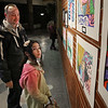 MIKE SPRINGER/Staff photo<br /> Third-grader Taya McDargh and her father, Todd, look at artwork together during a Derry School District art show opening last Wednesday, March 4, at Pinkerton Academy.<br /> 3/4/2020