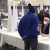 TIM JEAN/Staff photo<br /> <br /> Poll workers sit behind plexiglass and help voters pick up ballots before they can cast their vote on Election Day in Londonderry, NH. Turnout was heavy in the morning then was steady throughout the day.  11/3/20
