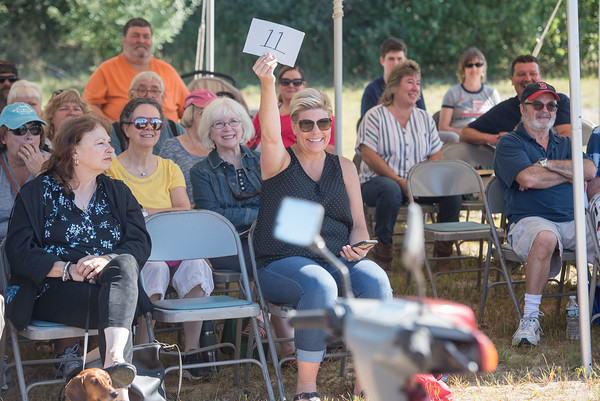 AMANDA SABGA/Staff photo  Carrie Peabody of Auburn excitedly bids on a moped scooter during the 41st Annual Derry Rotary Club Auction at the Fireye parking lot in Derry.   8/24/19