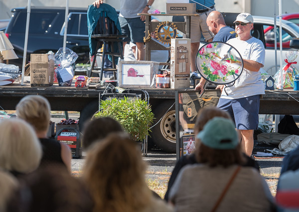 AMANDA SABGA/Staff photo  Rotarian Brian Germaine shows off a coffee table for auction during the 41st Annual Derry Rotary Club Auction at the Fireye parking lot in Derry.   8/24/19
