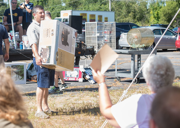 AMANDA SABGA/Staff photo  Rotarian Pete March showcases a fire pit for auction during the 41st Annual Derry Rotary Club Auction at the Fireye parking lot in Derry.   8/24/19