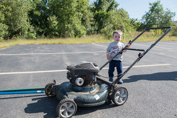 AMANDA SABGA/Staff photo  14-month-old Noah Spaulding of Derry checks out a lawn mower for auction during the 41st Annual Derry Rotary Club Auction at the Fireye parking lot in Derry.   8/24/19