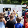 TIM JEAN/Staff photo<br /> <br /> Lt. Tyler Adcox, right, passes out information to children as they wait to pick up a free lunch from the Salvation Army Emergency Canteen vehicle in Derry. The Derry chapter offers free lunches from its canteen truck during the summer.   8/6/20