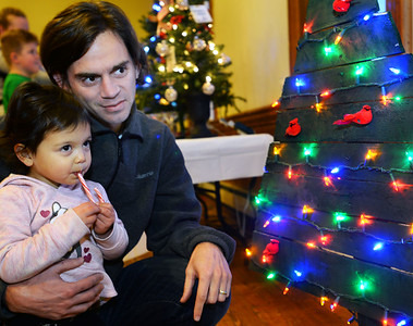 CARL RUSSO/Staff photo. Tom Fiferna of Derry shows his  daughter Nora, 3 one of the trees while she enjoys a candy cane. The Annual Festival of Trees at Upper Village Hall was held Saturday to support Upper Room family resource center in Derry. 12/15/2018