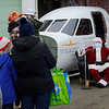 TIM JEAN/Staff photo<br /> <br /> Children wait with their parents in line to tell Santa Claus what her would like for Christmas during an outdoor event Saturday morning at the Aviation Museum of New Hampshire. Santa Claus arrives by helicopter at the museum, that is located in the historic 1937 airport terminal at the Manchester-Boston Regional Airport.   12/12/20