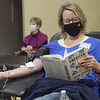 TIM JEAN/Staff photo<br /> <br /> Lori Muller of Derry, reads a book while giving blood during the Derry police annual winter blood drive held at the Calvary Bible Church in Derry, NH.  1/15/21