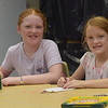 TIM JEAN/Staff photo<br /> <br /> Camryn Odachowski, 10, left, and her sister Kendall, 7, look up while making and coloring an owl in the craft area during Londonderry's Recreation Summer playground program held at South Elementary School.      7/22/21