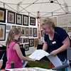 TIM JEAN/Staff photo<br /> <br /> Featured artist Tina Gagnon, of Salem, a color pencil artist whose work captures the vivid colors found in nature gives Addison Gauvain, 6, of Londonderry a coloring page after making a purchase from her booth during the Derry Homegrown Farm and Artisan Market in downtown Derry, NH.    6/2/21