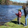 JULIE HUSS/Staff photo <br /> Evan Brissette , 5, reels in his line with a bit of help from his mother Amanda during Saturday's youth fishing derby in Derry.