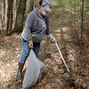 TIM JEAN/Staff photo<br /> <br /> Karyn Hynd picks up debris in the wooded area near the Brandy Brow Road sand pit during an Earth Week cleanup Sunday morning. Dozens of volunteers picked up debris, in and around the sand pit and wooded area near the East Meadow River.  4/18/21