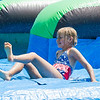 AMANDA SABGA/Staff photo<br /> <br /> Angela Muccitelli-Hull, 8, slides to a stop on an inflatable water slide kids cool down during the Haverhill Recreation Department's summer camp annual field day at Riverside Park.  <br /> <br /> <br /> 8/7/18
