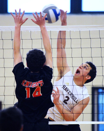 CARL RUSSO/Staff photo. Haverhill's A J Tamburino spikes the ball over the net as North Andover's Jacob Colon reaches to block. Haverhill defeated North Andover 3-0 in boys volleyball action. 4/26/2019