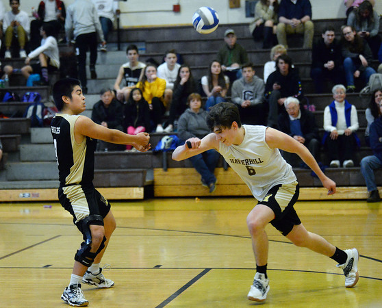 CARL RUSSO/Staff photo. Haverhill's Tuan Nguyen returns the serve as his teammate Connor Buscema gets out of his way. Haverhill defeated North Andover 3-0 in boys volleyball action. 4/26/2019