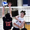 CARL RUSSO/Staff photo. Haverhill's Connor Buscema spikes the ball over the net as North Andover's Jacob Colon reaches to block. Haverhill defeated North Andover 3-0 in boys volleyball action. 4/26/2019
