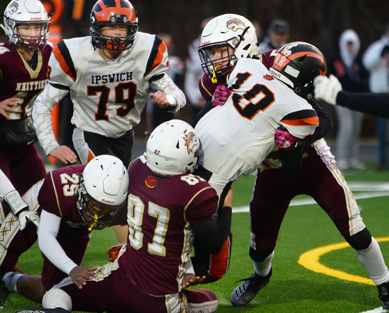 CARL RUSSO/Staff photo. Whittier's Nolan Mann, top, Jack Lemanier, 87 and Jeremias Collazo tackle Ipswich's Aiden Arnold. Whittier Tech was defeated 36-22 by Ipswich in Friday, November 8 football action. 11/8/2019