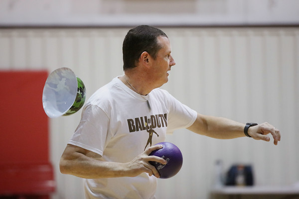 MIKE SPRINGER/Staff photo<br /> Haverhill assistant school superintendent Mike Pfifferling's helmet falls off as he throws a ball during the Chamber Business After Hours third-annual dodgeball tournament Wednesday at the Plaistow Community YMCA. The event collects food and gifts for the YMCA's Giving Trees, which are located in the lobbies of the Plaistow and Haverhill YMCAs. The collected items will be distributed to families in need.<br /> 11/20/2019