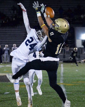 CARL RUSSO/Staff photo. Haverhill's Teyshon McGee leaps high but is unable to make the catch as Lexington's Jayden Dillon breaks up the pass.   Haverhill defeated Lexington 42-28 in Friday night football action. 11/15/2019